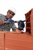stock photo of gad  - Mason chiseling away at brick - JPG
