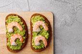 Sandwich With Guacamole And Shrimp On Cement Background poster