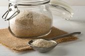Heap Of Psyllium Husk Also Called Isabgol In Metal Spoon And Glass Jar On White Table Background. Ps poster