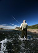 foto of catch fish  - fisherman standing in river with a fish on the line - JPG