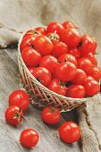 Fresh Red Tomatoes In A Wicker Basket On An Old Wooden Table. Ripe And Juicy Cherry Tomatoes With Dr poster