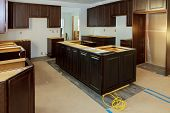 Installing Cabinets In A Kitchen Of Dark Color In The Process Of Completing The Kitchen Installation poster