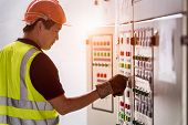 Electrician Looking To Control Panel In The Workplace. Engineer Works In The Industrial Quality Cont poster
