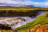 Picturesque multi-colored tundra on a sunny summer day. The most picturesque waterfall in Iceland -  poster