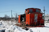picture of caboose  - An Abandoned and burned out Caboose sitting in a field - JPG