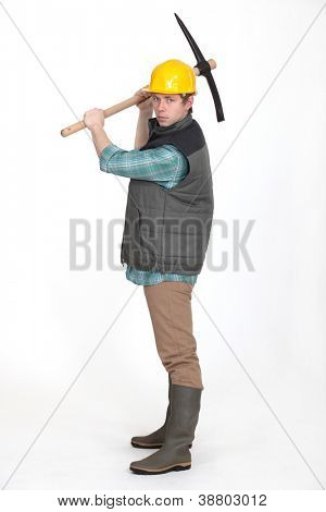 young bricklayer in profile holding pickaxe