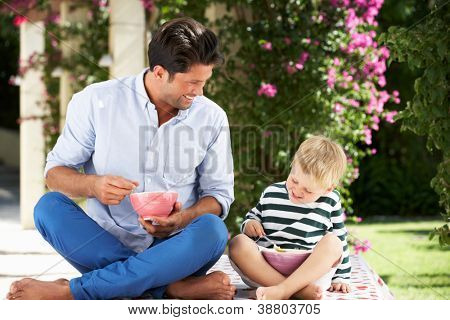 Father And Son Enjoying Breakfast Cereal Outdoors Together