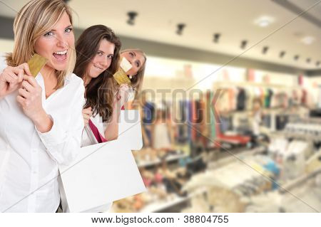 Three cute girls holding credit cards at the mall