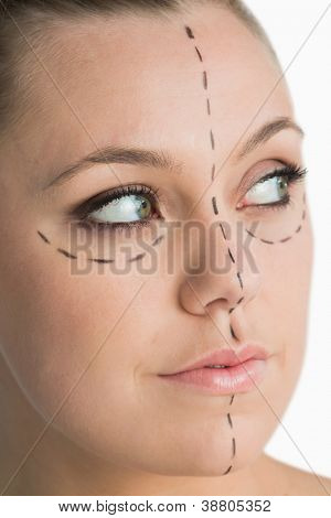 Blonde with marker on her face for facelift on white background