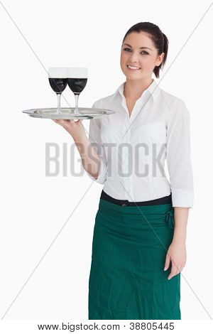 Smiling woman holding silver tray with glasses of red wine while directly looking into the camera