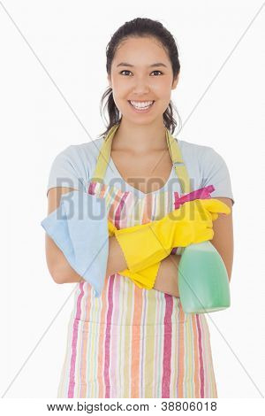 Woman standing with hands crossed holding cleaning products and smiling