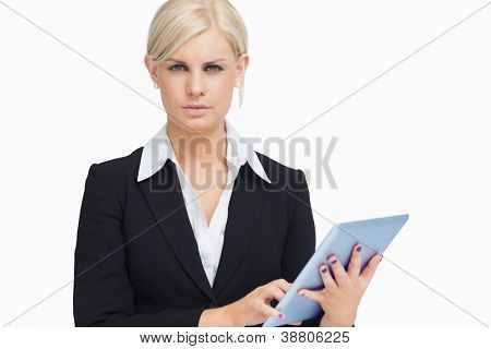Serious businesswoman holding a tablet computer against white background