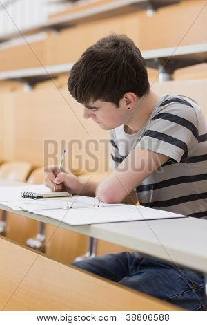 Concentrated student sitting at the lecture hall while writing