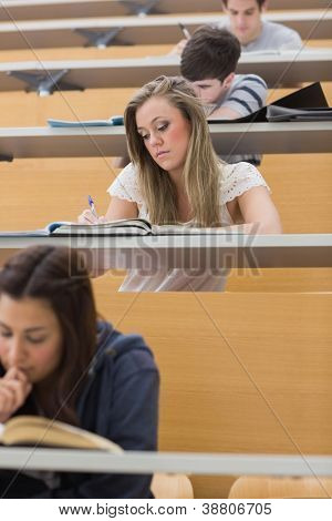 Students sitting at the lecture hall while writing and taking notes