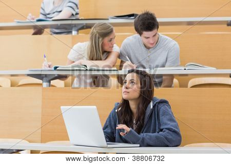 Students sitting at the lecture hall while girl thinking at laptop