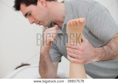 Physio manipulating the leg of a patient in a room