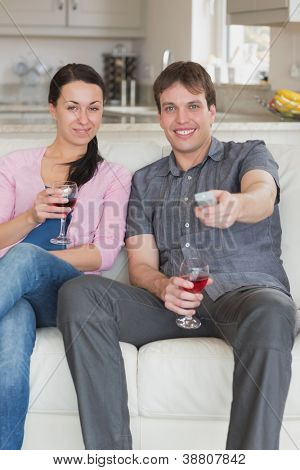 Two young people sitting in the living room while watching television