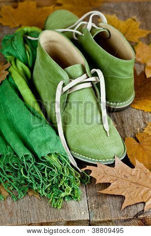 pair of green leather boots, scarf and yellow leaves on rustic wooden floor