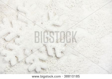 Snowflakes on snow background.