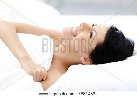 Laughing sexy girl tries to fall asleep in bed with white linen