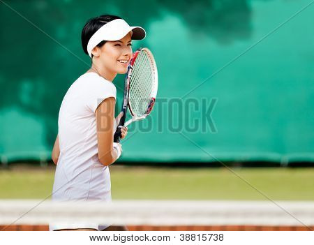 Sportswoman at the tennis court with racquet. Leisure
