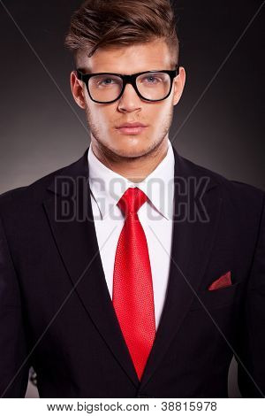 closeup portrait of a serious young business man looking at the camera, over dark background