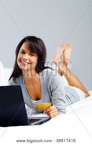 woman shopping online with credit card and laptop computer while sitting on bed at home isolated on grey background