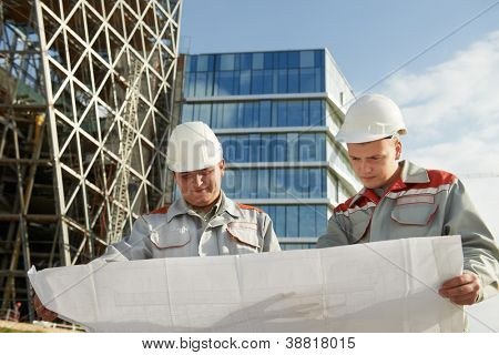 Two engineer builders site managers with blueprint plan at construction area