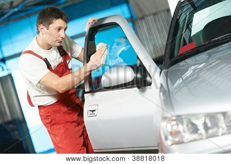 One young service mechanic cleaning automobile car door glass at auto repair shop