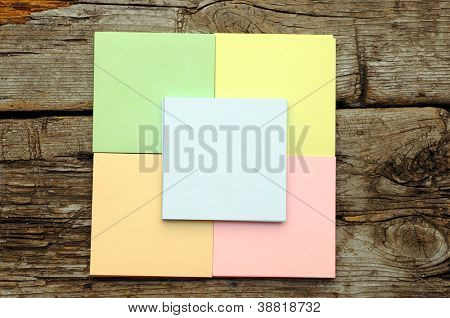 Stack of colorful sticky notes on wooden background
