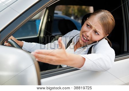 angry female driving the car, holding the mobile phone and screaming at someone