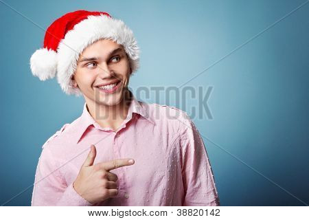 young cheerful christmas man with santa's hat point with hand left over blue background