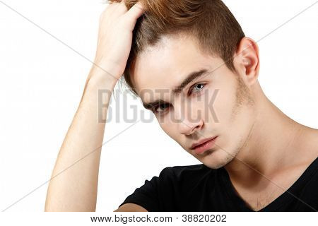 Handsome young man touching his hair, portrait of sexy guy looking at camera over white background