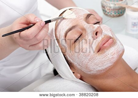 Beautician applying cream by brush on woman's face.