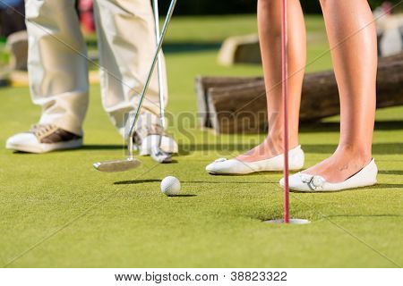 People, man and woman, only feet, playing miniature golf on a beautiful summer day