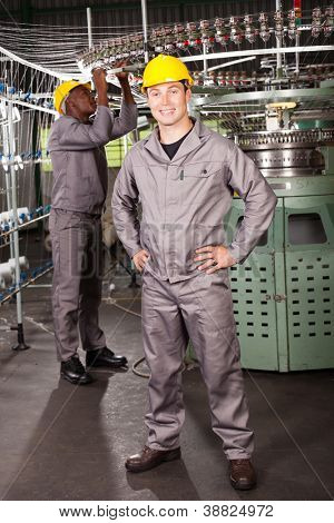 textile factory worker full length portrait in front of machine