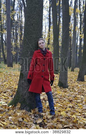 Girl in a red coat and jeans in the autumn park