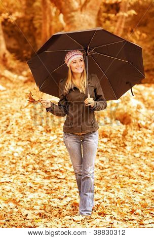 Photo of cute girl walk with stylish black umbrella in the autumn park