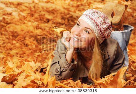 Image of cheerful teen laying down on the ground covered dry autumnal foliage in beautiful park
