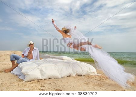 Happy Bride flying on bed to her husband on the beach