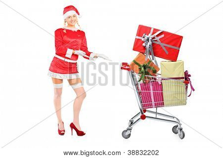 Full length portrait of a sexy woman wearing santa costume and showing a shopping cart full of presents isolated on white background