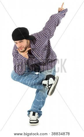 Smiling rapper in jeans and plaid shirt stands on one leg, props chin by his hand, points up by left hand isolated on white background.