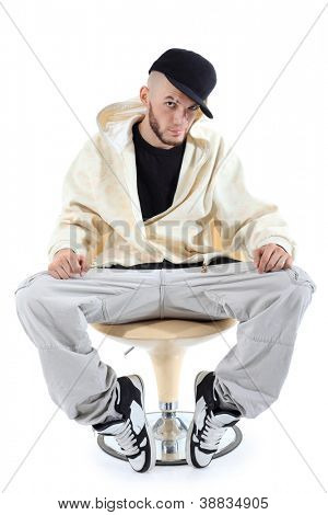 Rapper in yellow jacket sits on yellow chair and looks at camera isolated on white background.