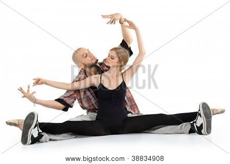 Ballerina in black and bald breakdancer sit on floor and portray puppets isolated on white background. Woman stretched legs in twine.