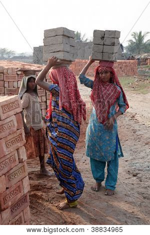 SARBERIA,INDIA, JANUARY 16: Brick field workers carrying complete finish brick from the kiln on January 16, 2009 in Sarberia, West Bengal, India.
