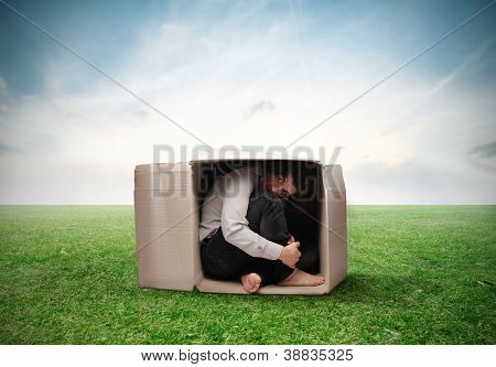 Man crouched in a box on a large grace field