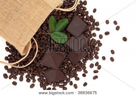 Coffee beans in a hessian drawstring sack and loose with leaf sprigs and dark chocolate over white background.