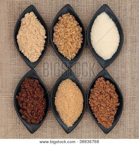 Selection of demerara, granulated, molasses, muscovado, crystal and light brown sugar in black  bowls over hessian background.
