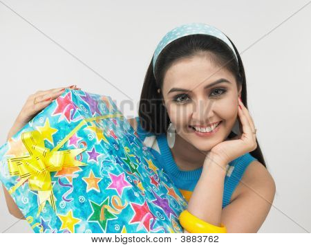 Young Asian Woman Of Indian Origin With A Gift Box