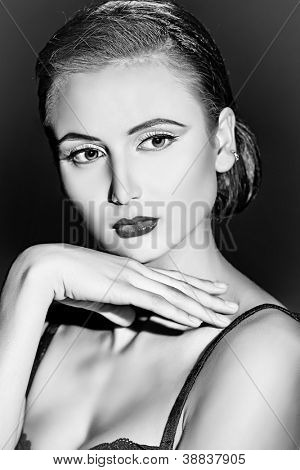 Portrait of a charming young woman over dark background. Light and shadow.